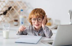 Ijverige leuke jongen die zijn thuiswerk voorbereiden Stock Fotografie