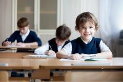 Ijverige studentenzitting bij bureau, klaslokaal Stock Afbeelding
