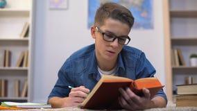 Ijverige tienerstudent die in glazen aan examens in universiteit voorbereidingen treffen, uiterste termijn stock videobeelden