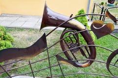 Ijzer bruine muzikale trompet, een pijp voor het spelen van muziek op een achtergrond van groen gras stock foto's
