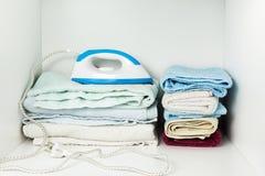 Ijzer en handdoeken in witte garderobe Stock Foto's