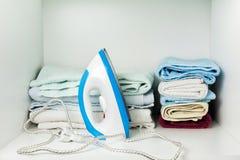 Ijzer en handdoeken in witte garderobe Royalty-vrije Stock Foto's