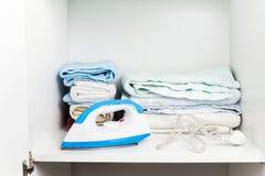 Ijzer en handdoeken in witte garderobe Royalty-vrije Stock Foto