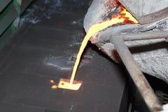 Ijzer gesmolten metaal het gieten in zandvorm stock afbeelding