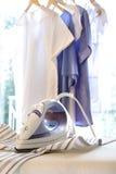 Ijzer op strijkplank met kleren het hangen Royalty-vrije Stock Foto
