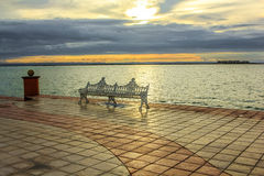 Ijzerbank op de waterkant bij zonsondergang Stock Foto's