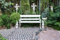 ijzerbank in tuin met kleine achtergrond Royalty-vrije Stock Afbeeldingen