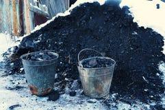 Ijzeremmers met steenkool dichtbij een kleine stapel van steenkool Stock Afbeeldingen