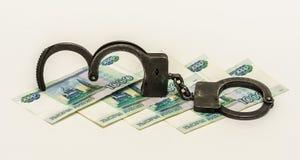 Ijzerhoudende metaalhandcuffs en bankbiljetten 1000 Russische roebels op w Royalty-vrije Stock Foto's