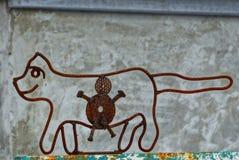 Ijzerkat op een omheining van oude roestige draad en bouten stock fotografie