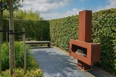 Ijzeropen haard met brandhout in de tuin Stock Foto's