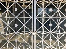 Ijzerpoorten, de omheining van de metaalbar op een sterke oude roestige ketting van verbindingen op een graanschuur groot slot da stock fotografie