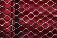 Ijzertextuur van een staalgrill op rode blinden op de deur Rode achtergrond royalty-vrije stock afbeeldingen