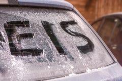 Ijzig achterruit van een auto met het Duitse woord voor ijs stock afbeelding