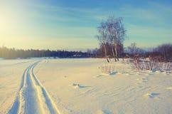 Ijzig de winterlandschap met sporen in sneeuw stock afbeeldingen