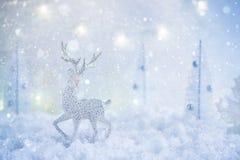 Ijzig de wintersprookjesland met stuk speelgoed herten, sneeuwval en magische lichten stock afbeeldingen