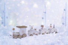 Ijzig de wintersprookjesland met stuk speelgoed trein, sneeuwval en magische lichten stock afbeeldingen