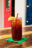 Ijzig Glas van Ijsthee met een Rood Stro en Citroen bij een Openluchtkoffie Stock Fotografie