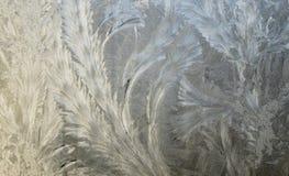 Ijzig Kerstmispatroon bij een de winterglazen venster Het patroon van het ijs op venster stock foto
