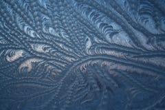 Ijzig patroon op zamerzshiesneeuw op de glaswinter stock fotografie