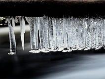 Ijzige takken boven het koelen stroom Bezinningen in ijskegels Stock Foto
