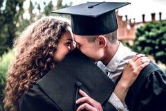 Ik ben blij dat wij deze mijlpaal konden samen delen De paargediplomeerden bevinden zich dichtbij universiteit en kus elkaar stock fotografie