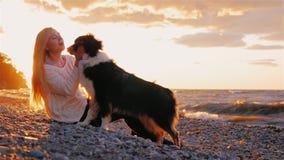Ik houd van mijn hond Jonge sobbaku van de blondevrouw laskat haar, kust haar stock footage