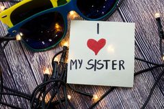 Ik houd van mijn zuster op Kleverig notadocument met zonnebril op een houten achtergrond met lichtenconcept voor het houden van v Stock Foto