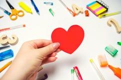 Ik houd van School! de student houdt het hart in zijn handen op de achtergrond van het bureau liefde van het leren De levering va stock afbeeldingen