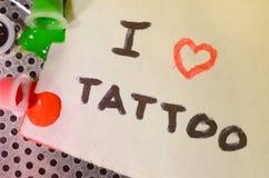 Ik houd van tatoegering De tekst wordt geschreven op een klein blad van document naast de ten val gebrachte kappen met gekleurde  royalty-vrije stock foto's