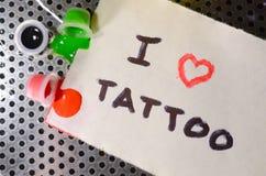 Ik houd van tatoegering De tekst wordt geschreven op een klein blad van document naast de ten val gebrachte kappen met gekleurde  royalty-vrije stock afbeeldingen