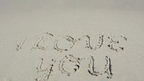 Ik houd van u geschreven in het zand stock footage