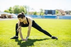 Ik zal sterk zijn Het mooie sportenmeisje is bezig geweest met een sportenstadion Het opwarmen van de spieren alvorens op te leid stock fotografie
