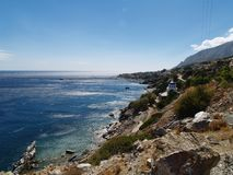 Ikaria sud coast. Mountainous sud coast of Ikaria island in Greece. In background are  Agios Kirikos port and a small chapel of Ascension with blue dome Stock Photo
