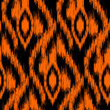 Ikat Ogee Background  66. Ethnic folk tribal seamless pattern Ikat Ogee, consisting of orange, red and black elements Stock Photo