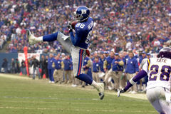 Ike Hilliard. Wide Receiver Ike Hillard of the New York Giants catches a   pass from New York Giants Quarterback Kerry Collins at the NFC Championship game.The Royalty Free Stock Images
