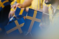 IKEA opening second store in Romania. Bucharest, Romania - June 24, 2019: Blurry image of Sweden flags holding by IKEA staff are seen in the opening day of the stock image