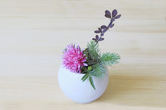 Ikebana with pink flower, branch, blue spruce and barberry in a white vase Stock Photos