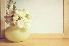 Ikebana und Weinlesefotorahmen auf Tabelle Stockfoto