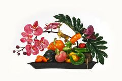 Ikebana from vegetables. Composition from colors of an orchid and fresh vegetables Stock Photography