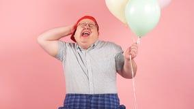 Iklädd barnslig stil för lycklig man som joyfully skrattar, medan rymma luftballonger, ultrarapid arkivfilmer