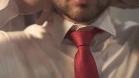 Iklädd brutal skäggig man en härlig bröllopdag Brudgummen bär ett rött band runt om hans halsnärbild stock video