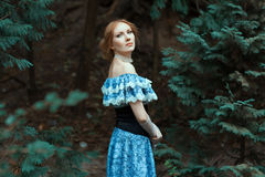 Iklädd flicka en gammalmodig blåttklänning Arkivfoto