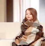 Iklädd flicka ett filtsammanträde på soffan Arkivfoto