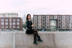 Iklädd flott kläder för ung attraktiv kvinna som poserar, medan sitta utomhus med mobiltelefonen, royaltyfria foton