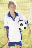 Iklädd fotboll Kit Standing By Goal för ung pojke Royaltyfri Fotografi