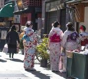 Iklädd kimono för ung japansk kvinna som går i marknad, med baksida till kameran royaltyfria bilder