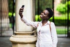 Iklädd moderiktig tillfällig dräkt för attraktiv afro för amerikan som blogger för ung kvinna gör selfie via smartphonen för att  royaltyfria bilder
