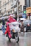 Iklädd rainwear för kinesisk kvinna på encykel porslin shanghai Royaltyfri Fotografi