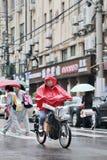Iklädd rainwear för kinesisk pojke på encykel, Shanghai, porslin Royaltyfri Fotografi